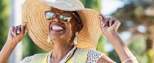 Smiling senior woman wearing sunglasses and big straw hat